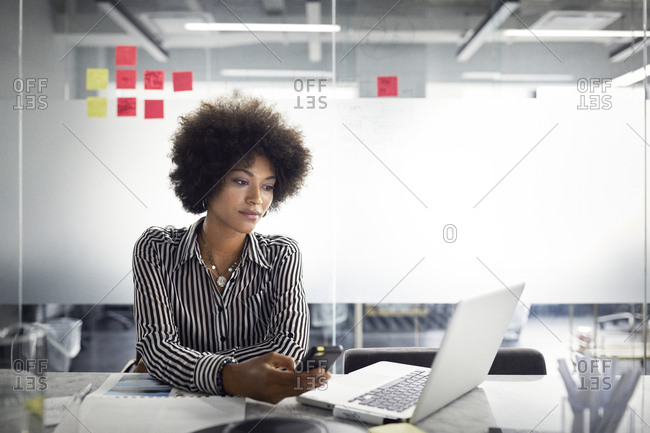 Businesswoman looking at laptop computer while holding smart phone in office