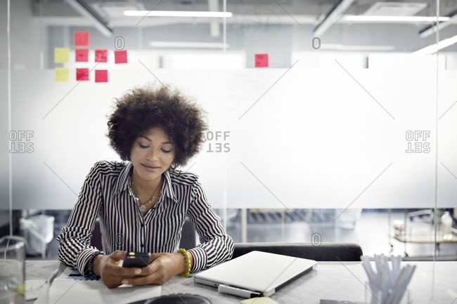 Businesswoman using smart phone while sitting in office
