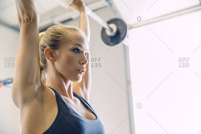 Close-up of young woman lifting barbell while exercising in brightly lit gym