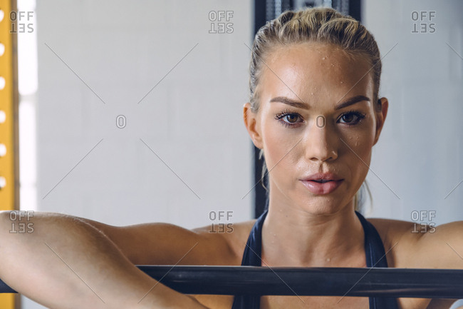 Portrait of confident woman sweating while exercising in gym