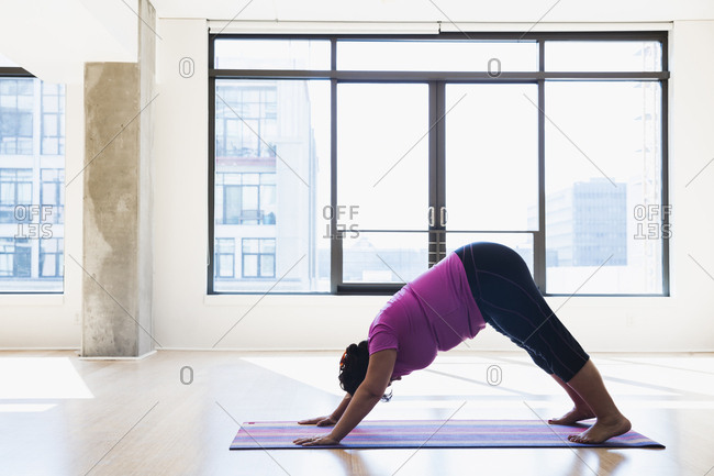 Side view of woman practicing downward facing dog position yoga against window