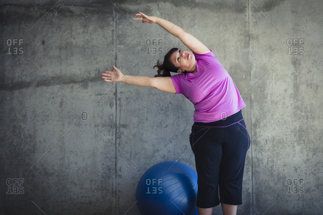 Woman with arms raised practicing yoga while standing by fitness ball against wall in studio