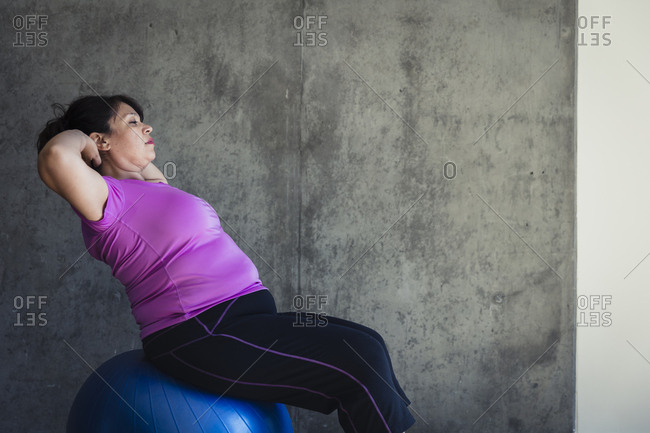 Woman with hands behind head sitting on fitness ball against wall in yoga studio
