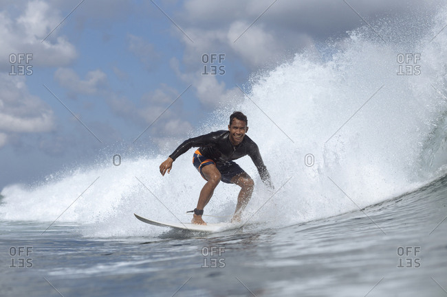 Portrait of happy man surfing on sea against cloudy sky