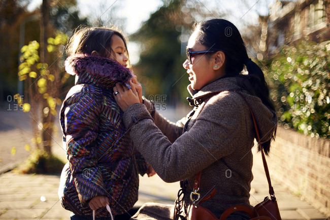 Mother helping daughter in wearing winter coat at footpath