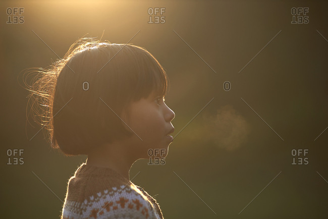 Close-up of girl exhaling breath vapor while looking away during sunny day in winter