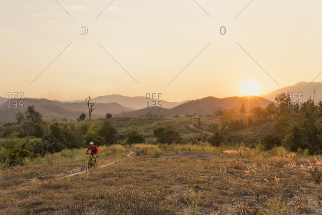 High angle view of man riding mountain bike on field against sky during sunset
