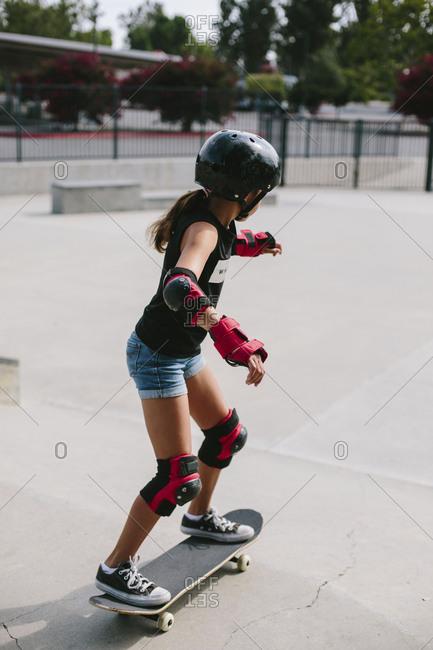 Side view of girl skateboarding at park