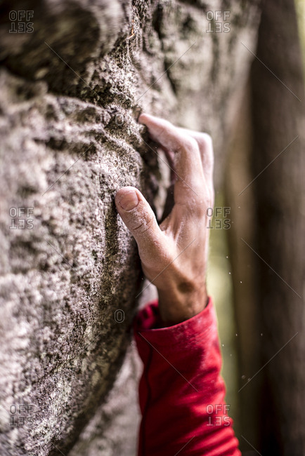 Cropped hand of man gripping on rock while bouldering