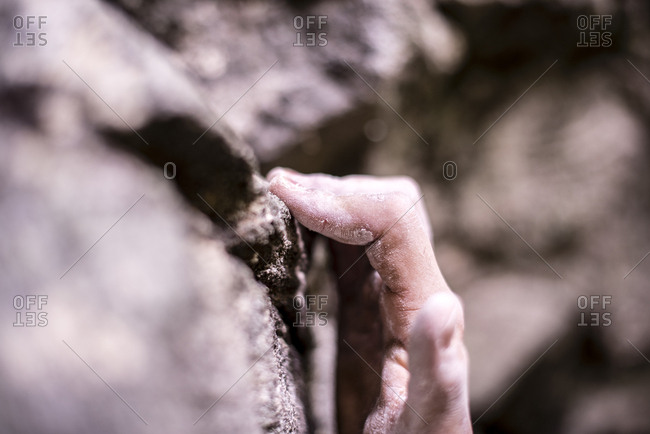 Close-up of cropped hand gripping on rock while bouldering