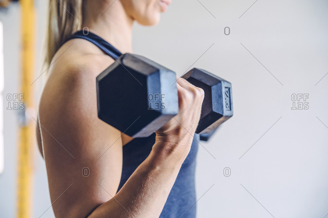 Close-up of midsection woman lifting dumbbells while exercising against wall in gym