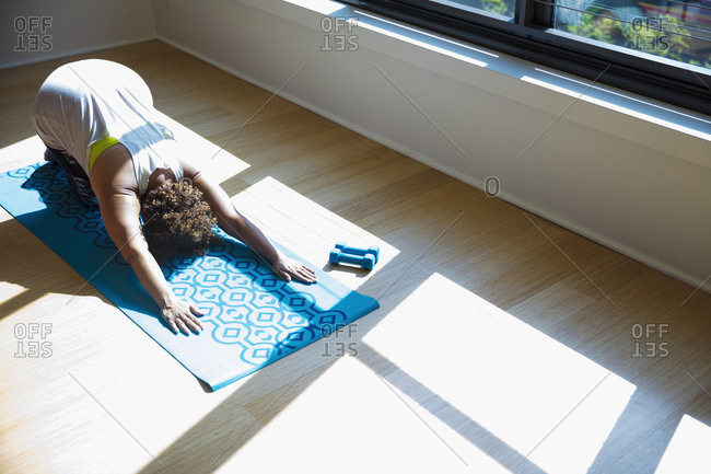 High angle view of woman practicing yoga on exercise mat in studio