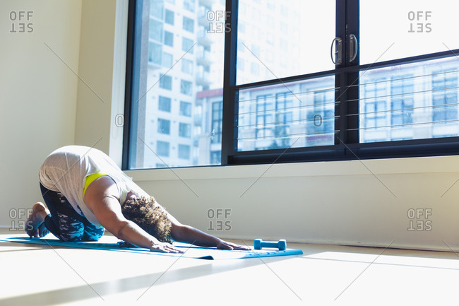 Woman practicing yoga on exercise mat against window in studio