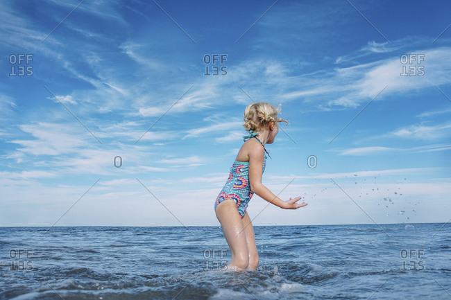 Side view of girl playing while standing in sea against cloudy sky