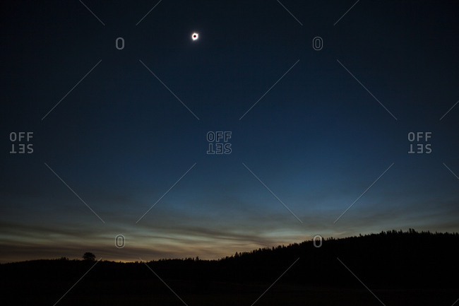 Scenic view of solar eclipse against sky over landscape during sunset