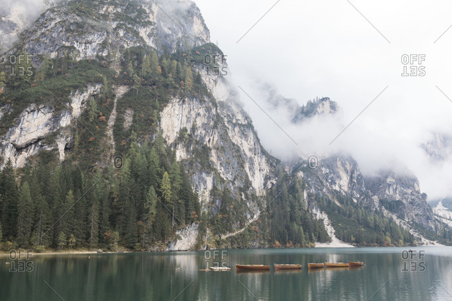 Several wooden boats moored in Lake Prags, Italy