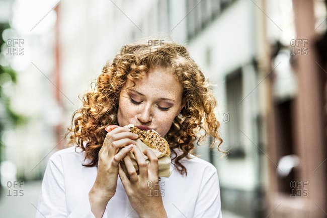 Portrait of young woman eating bagel outdoors