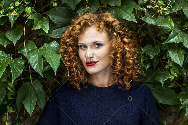 Portrait of redheaded young woman with red lips