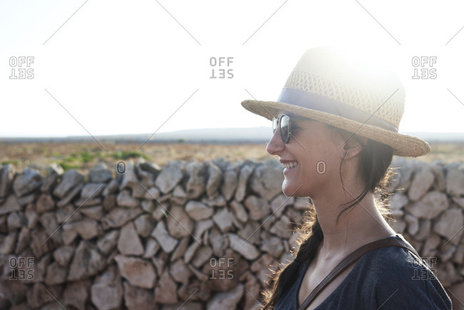 Spain- Menorca- happy single traveller wearing straw hat and sunglasses at backlight