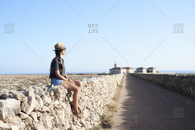 Spain- Menorca- single traveller sitting on natural stone wall looking at view