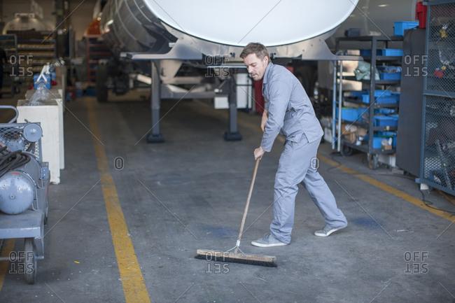 Industrial worker sweeping floor