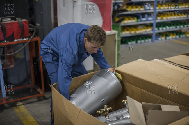 Industrial worker packing away metal container