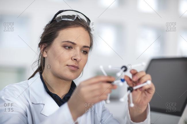 Scientist working in lab holding molecular structure