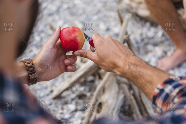 Man's hand cutting apple at camp fire