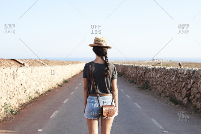 Spain- Menorca- back view of single traveller on county road