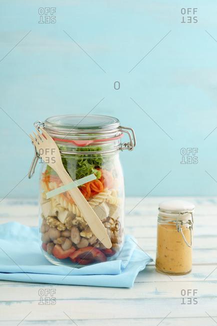 Preserving jar of vegan mixed salad with tofu and pasta and jar of cocktail sauce