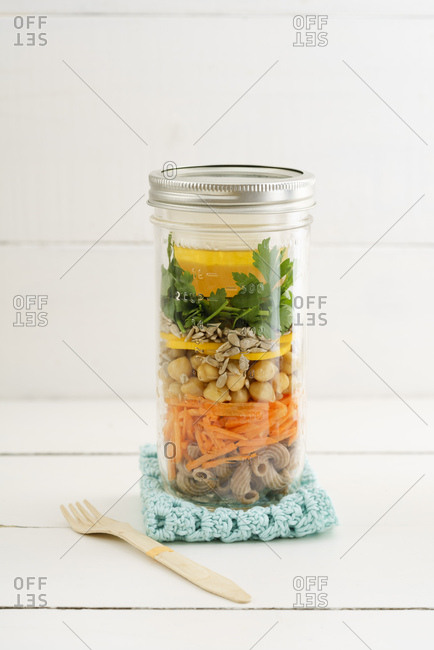 Jar of vegan mixed salad with whole-grain noodles- chickpeas and vegetables