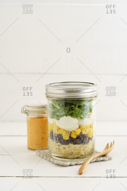 Jar of vegetarian mixed salad with Kritharaki- corn- rocket and cranberries and jar of cocktail sauce