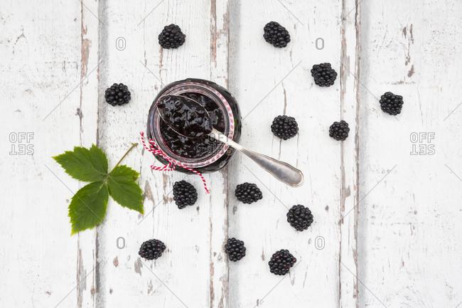 Glass of homemade blackberry jam- blackberries and leaf on wood
