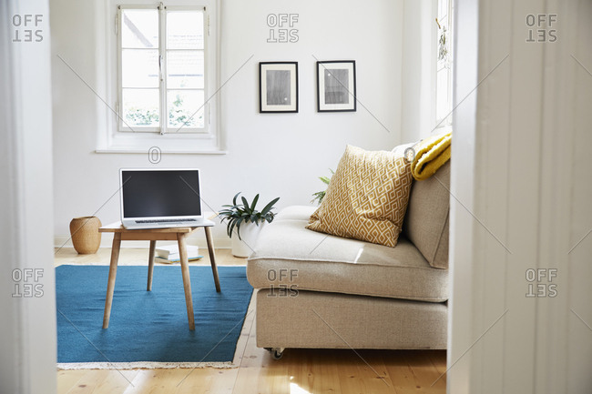 Laptop on coffee table in a bright modern living room in an old country house