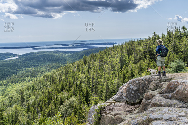 Hiker looks out toward the ocean from a peak in Acadia National Park, Maine