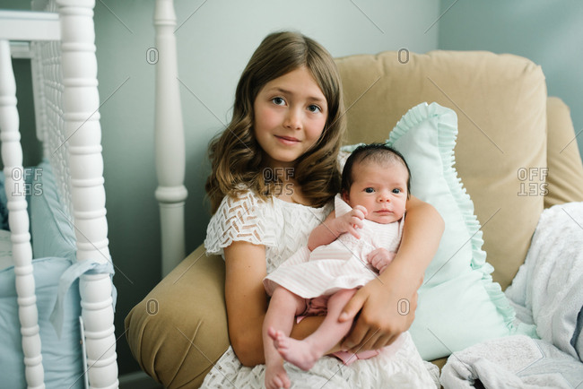 Girl sitting in chair holding newborn baby