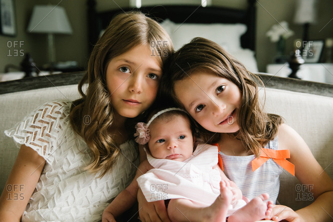 Sisters holding newborn baby