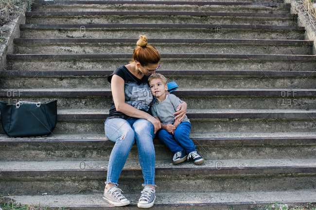 Mother sitting on outdoor steps with her arm around her son