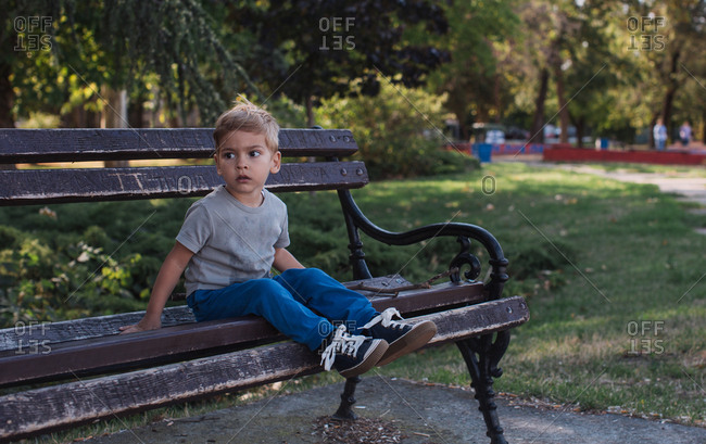 Boy sitting on a park bench looking to the side