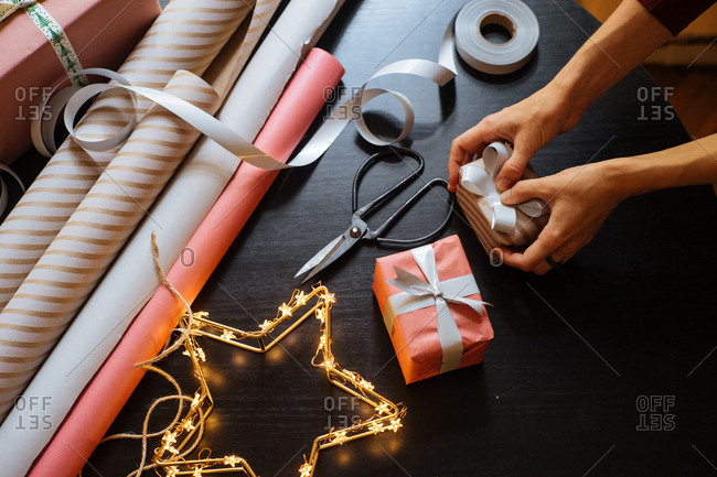 Woman putting a bow onto a Christmas gift