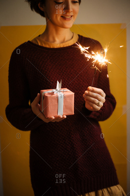 Woman holding a present and a star shaped sparkler