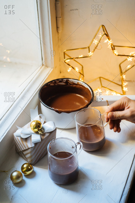 Woman grabbing cup of thick hot chocolate beside Christmas gift