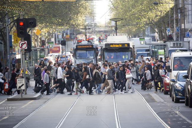 Melbourne, Australia - September 26, 2017: Busy crowd crossing Collins street in Melbourne, Australia
