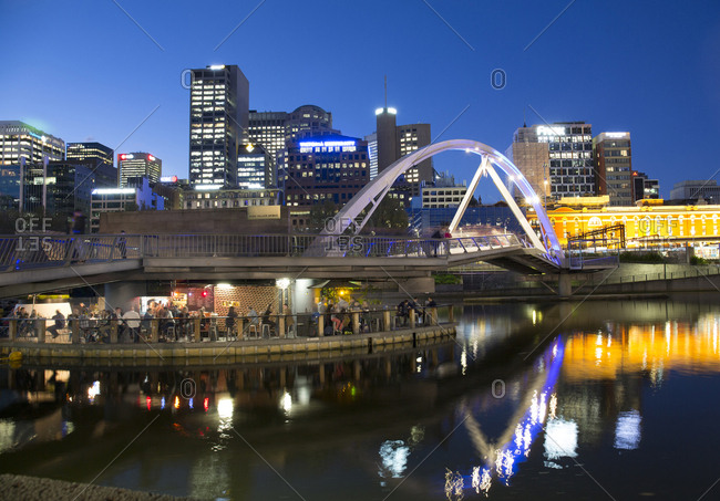 Melbourne, Australia - September 27, 2017: Pedestrian bridge over Yarra with bar underneath at night