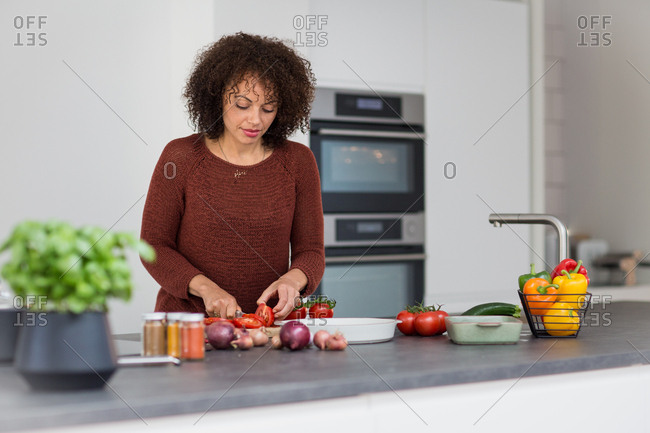 African American female chopping tomatoes