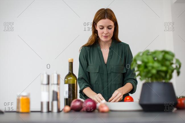 Adult female preparing meal with fresh ingredients