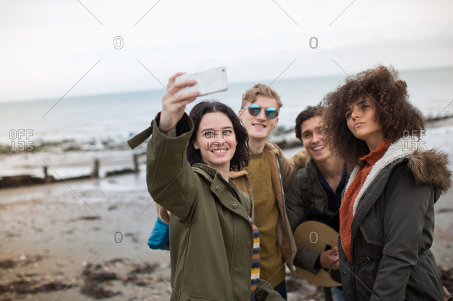 Group of young adult friends taking a selfie on a beach in winter