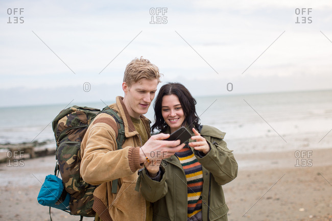 Young couple using smartphone on a winter break at beach