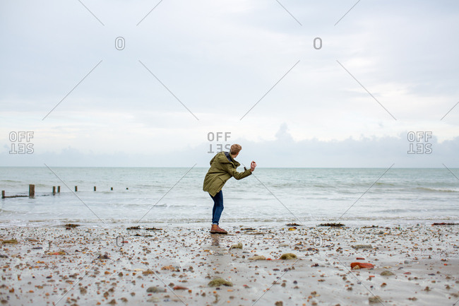 Young male skimming stones on a beach in winter