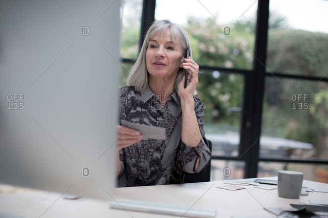 Senior businesswoman working in office using smartphone